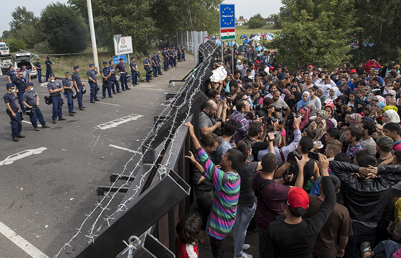 Migrants stand in front of a barrier at the border with Hungary near the village of Horgos, Serbia, on September 16, 2015. Photo courtesy of REUTERS/Marko Djurica *Editors: This photo may only be republished with RNS-GUSHEE-COLUMN, originally transmitted on September 16, 2015.