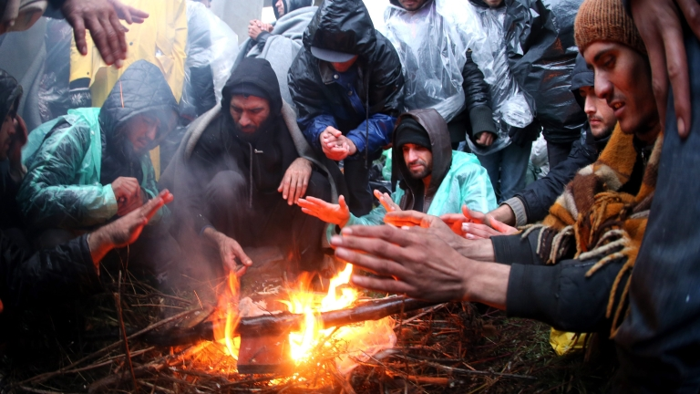 epaselect epa05628443 Migrants try to warm up under the overpass on the freeway near Pecinci 50km from Belgrade, Serbia, 12 November 2016. Hundreds of migrants march from Belgrade to Croatian border on the highway Belgrade-Zagreb. According to reports, hundreds of migrants from Middle East countries marched through the Serbian capital, apparently trying to move towards Croatia, in order to reach western European countries.  EPA/KOCA SULEJMANOVIC