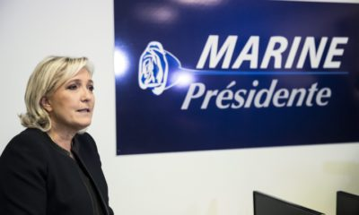 epa05633472 French far right party leader Marine Le Pen sits next to her campaign sign as she launches her campaign for the French presidential elections of 2017 in Paris, France, 16 November 2016.  EPA/ETIENNE LAURENT