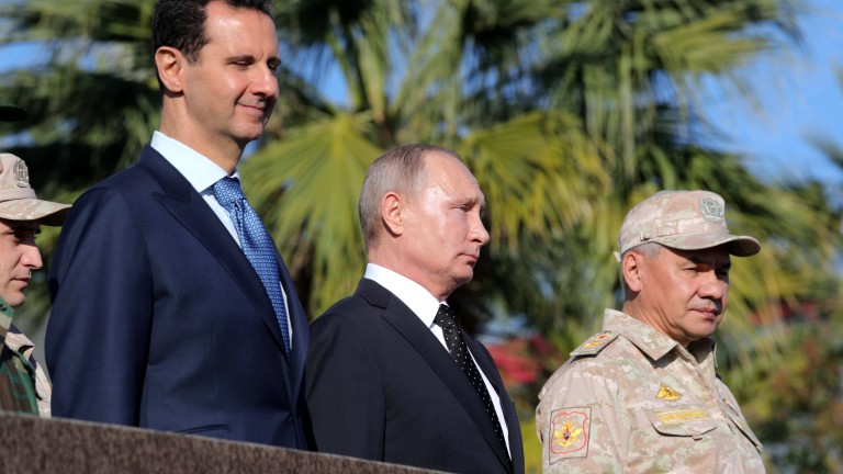epa06382940 Russian President Vladimir Putin (C), Russian Defence Minister Sergei Shoigu (R) and Syrian President Bashar al-Assad (L) visit the Hmeimim (also Khmeimim) Air Base, south-east of the city of Latakia in Syria, 11 December 2017. Media reports state Russian President Vladimir Putin made an unannounced visit to Syria where he met with Syrian Presidents Bashar al-Assad and ordered a withdrawal of Russian troops from Syria.  EPA/MICHAEL KLIMENTYEV / SPUTNIK / K MANDATORY CREDIT
