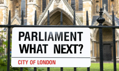 Sign in the style of a London Street sign asking Parliament, what next? Black white and red banner against wrought iron railings, with Westminster Abbey in the background.