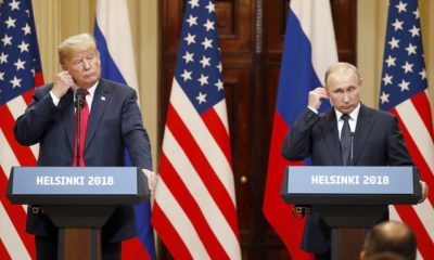 epaselect epa06893404 US President Donald J. Trump (L) and Russian President Vladimir Putin (R) adjust their earpiece plugs during a joint press conference following their summit talks at the Presidential Palace in Helsinki, Finland, 16 July 2018.  EPA/ANATOLY MALTSEV