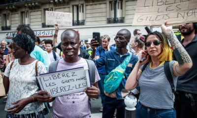 epa07714270 Human rights activists and memebers of the 'Black Vests' movement holds posters reading 'Free Black Vests' as they gather in front of a police station, where other activists have been detained in custody in Paris, France, 13 July 2019.  Hundreds of undocumented migrants calling themselves 'black vests' (gilets noirs) stormed the Pantheon monument in Paris on 12 July 2019 to demand right to stay in France.  EPA/CHRISTOPHE PETIT TESSON