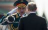 In this photo taken on Monday, May 9, 2016, Russian Defense Minister Sergei Shoigu, left, salutes to Russian President Vladimir Putin, back to a camera, prior the Victory Day Parade on the Red Square, which commemorates the 1945 defeat of Nazi Germany in Moscow, Russia. Shoigu says the airstrikes were suspended starting from 10 a.m. on Tuesday, Oct. 18 and the suspension is intended to prepare for the opening of humanitarian corridors for the rebels to leave the besieged city of Aleppo. (AP Photo/Alexander Zemlianichenko)