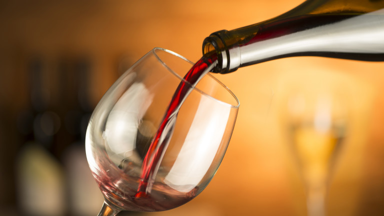 Bottle is pouring red wine in a glass